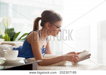 Pretty lady in eyeglasses reading paper book while lying on cozy sofa at home. Relaxed young woman resting in living room, enjoying interesting novel at day off. Female student studying with textbook poster