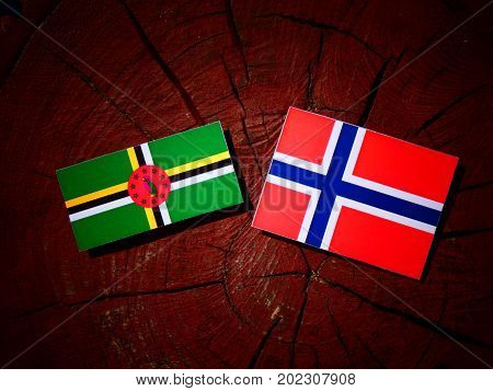 Dominica Flag With Norwegian Flag On A Tree Stump Isolated
