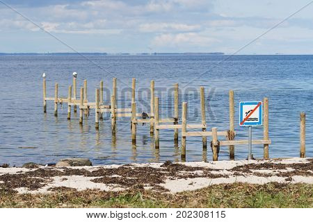 Remains of an old wooden pier in Langeland, Denmark with a sign saying no jumping from the pier
