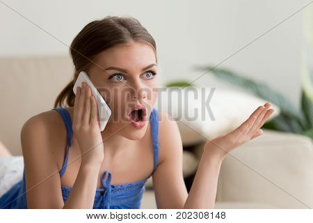 Surprised young woman talking on mobile phone, confused after hearing unbelievable news on cellphone, shocked girl because of unexpected call. Abruptness, quarrel and affront during phone conversation