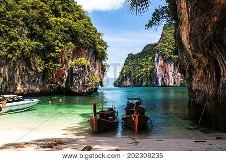 Longtail boat on the beach surrounded by cliffs on the island of Koh Lao La Ding. Krabi Thailand