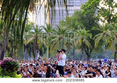 Bangkok Thailand - February 05th 2017: A photographer among the crowd of spectators on the concert of Royal Bangkok Symphony Orchestra in the Lumpini Park.