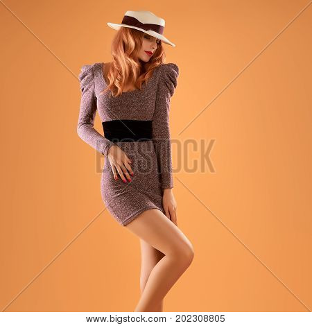 Fall Fashion. Model Woman in Autumn Outfit. Stylish Dress, Trendy Hat, Wavy Hairstyle. Fashion autumn Lady. Glamour Playful Redhead Sexy Girl, Fashion Pose. Fall Concept. Vintage Retro Pinup