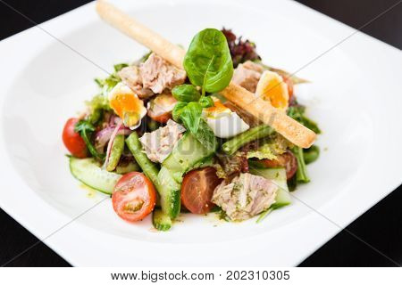 Salad nicoise. Tuna with baby potatoes, eggs, beans, tomatoes olives and parsley
