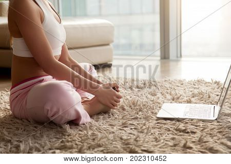 Close up photo of woman in sportswear sitting on carpet in living room and doing butterfly stretch. Lady watching yoga exercises online video tutorial and trying to do seated bound angle yoga pose