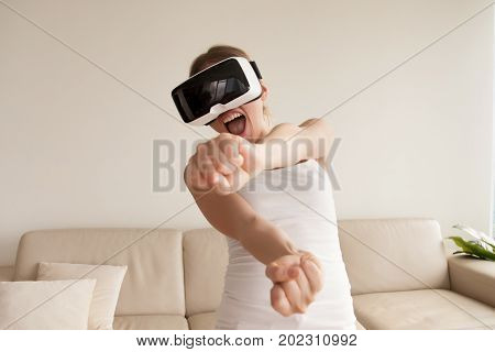 Excited young woman in VR goggles driving car in virtual reality. Lady screaming when turning virtual steering wheel, teen playing in racing computer game or road simulator, enjoying 3d gaming at home