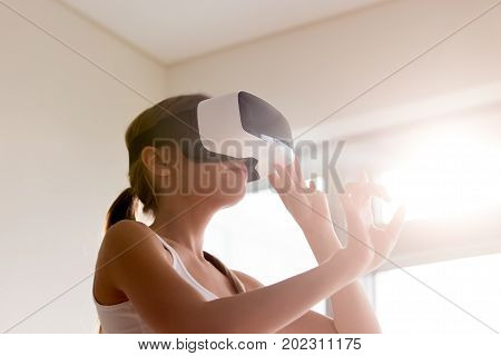 Young woman wearing virtual reality glasses and touching objects in 3d world, choosing goods and shopping in virtual store, working in augmented reality. Lady interacting with digital simulation app