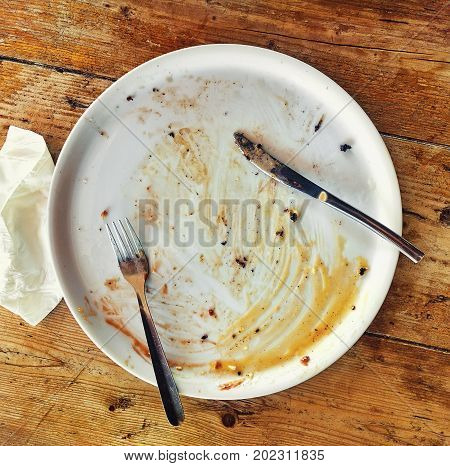 Empty dirty plate with fork and knife on the wooden table and crumpled napkin