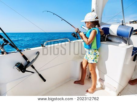 Lovely little girl with a fishing rod fishing from the boat