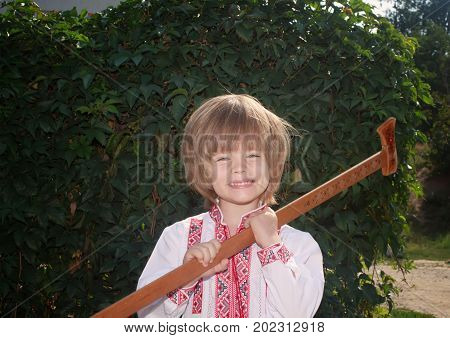 Portrait of a little boy in a white embroidered shirt with a wooden vintage hatchet outdoors