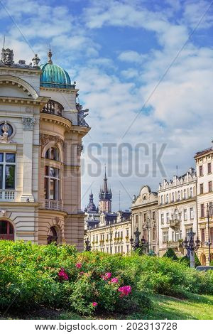 Cityscape of Krakow old town, part view of Theater building, Szpitalna street and town hall on a sunny summer day with blue sky and blooming tea rose bushes
