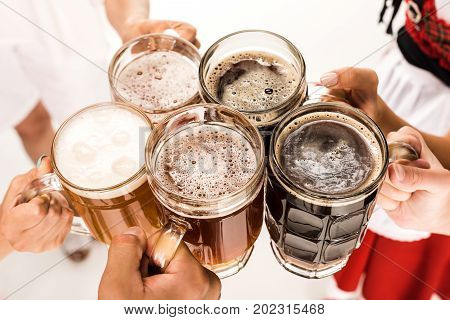cropped view of hands clinking with beer glasses isolated on white