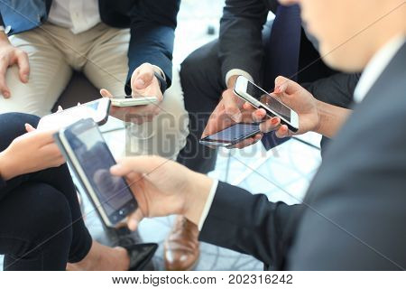 Group of people using smart phones sitting at the meeting, close up on hands
