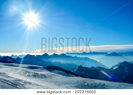 Snow tops of high Mount Elbrus at sunset, mountain landscape, sights and nature.