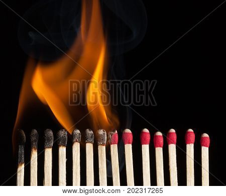 A line of red safety matches showing burnt out matches on the left through burning matches ignition and unused ones on the right. poster
