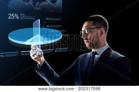 business, augmented reality and future technology concept - businessman in glasses working with transparent tablet pc computer and virtual charts projections over black background