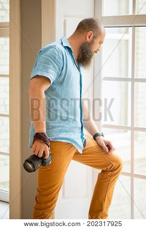 portrait of man near window. Profassional photographer hold in hand photo camera. caucasian man with beard look through window frame. Full-lenght window Man staying