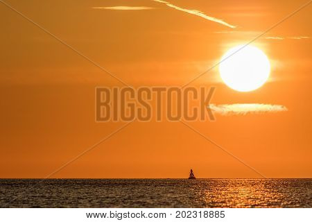 Zen sky. Beautiful sunrise with clear orange sky above calm sea and solitary buddha shaped buoy. Tropical vacation getaway at sea.