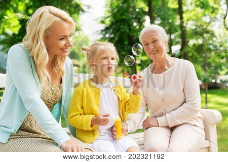 family, generation and people concept - happy smiling woman with senior mother and little daughter blowing soap bubbles at park