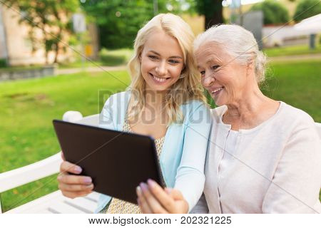 family, technology and people concept - happy smiling young daughter with tablet pc computer and senior mother sitting on park bench
