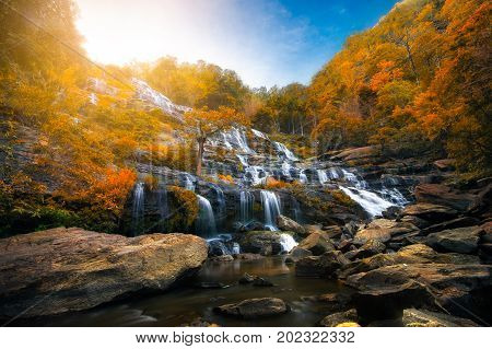 Mae Ya Waterfall is beautiful with colorful trees of autumn natural of Doi-Inthanon at Chiang Mai province in Thailand and very popular for photographers and tourists.