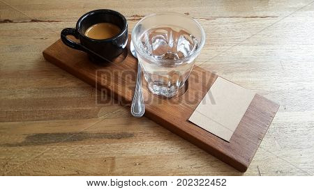 espresso coffee shot in black cup on the wooden plate with cupping note and copy space