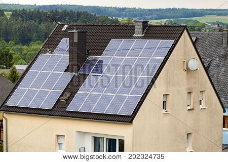 Renewable clean green energy saving efficient solar panels on suburban house roof.