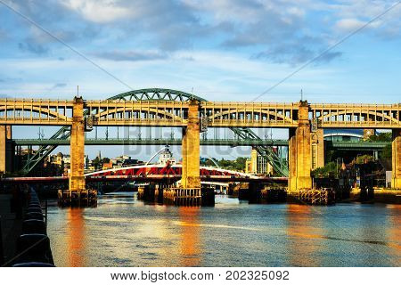 Newcastle upon Tyne, UK. The High Level Bridge in Newcastle upon Tyne, UK, over river Tyne during daytime with the Tyne Bridge behind it. Cloudy sky