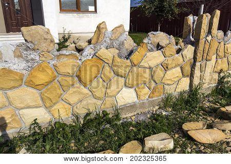 Construction of limestone fence near residential house. Stone masonry