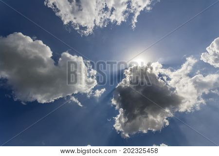 Rays of sun shining through white puffy clouds and blue sky
