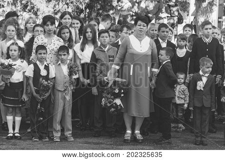 Adygea Russia - September 1 2017: children with bouquets of flowers enrolled in the first class at school on the solemn line in the day of knowledge black and white photo