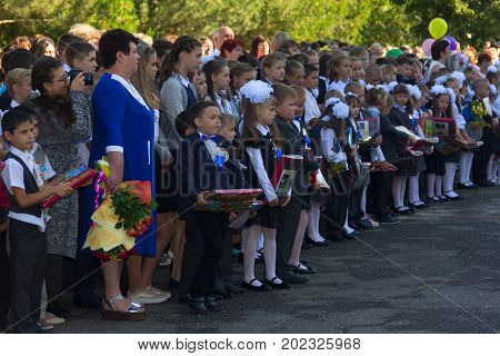Adygea Russia - September 1 2017: children enrolled in the first class with gifts in the hands of teachers and high school students on the school's solemn line in the day of knowledge