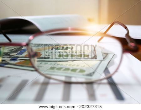 The US dollars see through glasses lens on financial graph workplace of the business. Concept of business and finance.