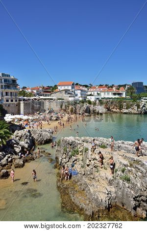 CASCAIS PORTUGAL - JUNE 07 2017: People relaxing on the Praia da Rainha public beach. Cascais is famous and popular summer vacation spot for Portuguese and foreign tourists