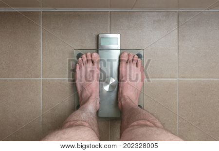 Man's Feet On Weight Scale -