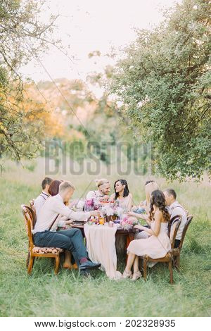 The vertical photo of the wedding dinner with the newlyweds and guests celebrating the ceremeny in the sunny forest poster