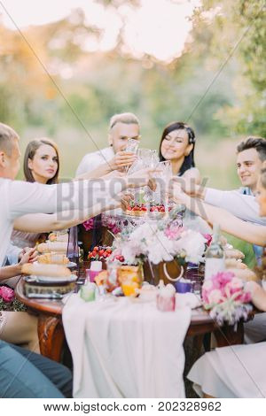The close-up photo of the newlyweds and guests clinking their glasses and sitting at the table full of delicious food and peonies poster