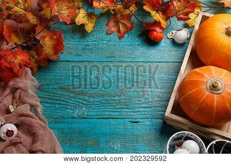 Wooden table with halloween pumpkin, maple leaf, eyeballs