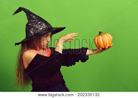 Girl With Carved Orange Pumpkin Isolated On Green Background
