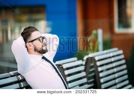 Relaxed Business Man Sitting On A Bench With Hands Over Head And Enjoy Free Time After Success