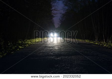Male silhouette at the edge of a dark mountain road through the forest in the night. Scenic night landscape of dark blue sky. Man standing on the road against the light of car headlights. The car on the roadside.