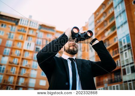 Handsome Business Man Looking With Binoculars Outdoors Near Building