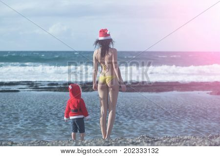 Girl in swim suit and boy wearing santa costume. Mothers day and family love. Winter holidays concept. Christmas and new year celebration. Woman and child standing on sea beach.