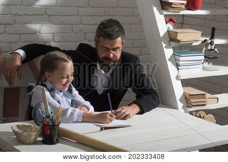 Kid and man sit by desk with school supplies. Schoolgirl and her dad with happy faces do homework. Back to school and home schooling concept. Girl and her father in classroom on white brick background