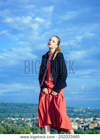 Woman relaxing on nature. Model in red tie and skirt. Girl posing on natural background. Fashion and accessories concept. Summer vacation and wanderlust.
