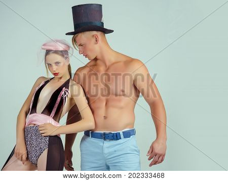 Woman or girl wearing sexy lingerie and veil hat. Fitness and beauty. Man or macho with muscular torso in black top hat. Fashion and style concept. Couple in love posing on grey background.