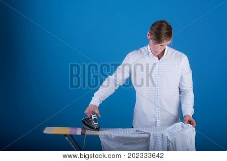 Macho wearing striped shirt. Ironing board on blue background. Guy using iron. Housework and fashion concept. Man ironing clothes.