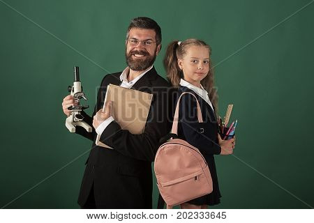 Man in suit and girl with bag wears uniform. Home schooling and back to school concept. Kid and dad hold microscope book and stationery. Father and schoolgirl with happy faces on green background