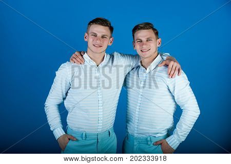 Happy men hugging. Two brothers smiling on blue background. Twins wearing striped shirts and pants. Models standing together. Family brotherhood and friendship concept.
