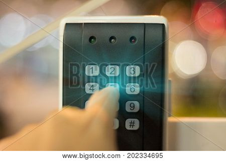 Human hand presses on the button entering security system code. Combination PIN code on keypad. Password house alarm. Digital combination lock wall.